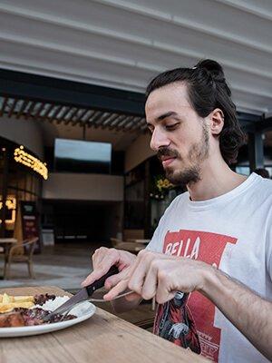 Hombre comiendo en Brasa y Leña